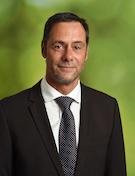 Porträt des Geschäftsführers Karsten Spinner im Anzug vor grünem Hintergrund